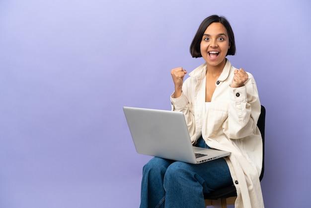 승자 위치에서 승리를 축하하는 보라색 배경에 고립 된 노트북과 의자에 앉아 젊은 혼혈 여자