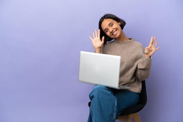 Молодая женщина смешанной расы сидит на стуле с ноутбуком, изолированным на фиолетовом фоне, считая девять пальцами
