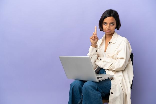 Молодая женщина смешанной расы сидит на стуле с ноутбуком, изолированным на фиолетовом фоне, считая одного с серьезным выражением лица