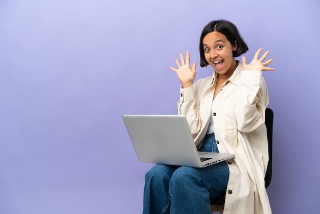 指で 10 を数える紫色の背景に分離されたラップトップで椅子に座っている若い混血女性