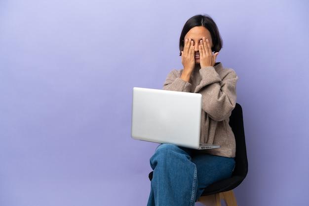 Молодая женщина смешанной расы сидит на стуле с ноутбуком, изолированным на фиолетовом фоне, прикрывая глаза руками Premium Фотографии