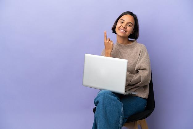 Молодая женщина смешанной расы сидит на стуле с ноутбуком, изолированным на фиолетовом фоне, делает приближающийся жест