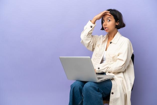 측면을 보면서 깜짝 제스처를 하 고 보라색 배경에 고립 된 노트북과 의자에 앉아 젊은 혼혈 여자