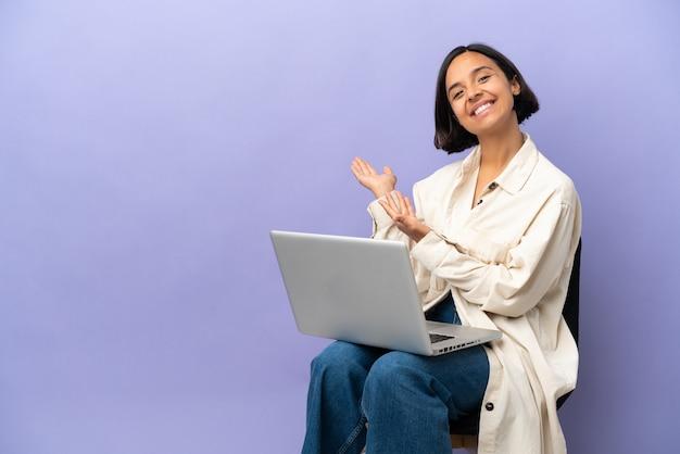 Молодая женщина смешанной расы сидит на стуле с ноутбуком, изолированным на фиолетовом фоне, протягивая руки в сторону, чтобы пригласить приехать