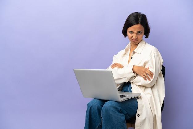 Молодая женщина смешанной расы, сидящая на стуле с ноутбуком, изолирована на фиолетовом фоне, чувствуя себя расстроенной