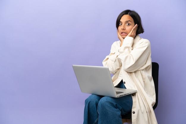 좌절과 귀를 덮고 보라색 배경에 고립 된 노트북과 의자에 앉아 젊은 혼혈 여자