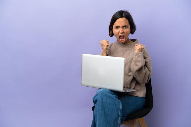 Молодая женщина смешанной расы, сидящая на стуле с ноутбуком, изолирована на фиолетовом фоне, разочарована плохой ситуацией