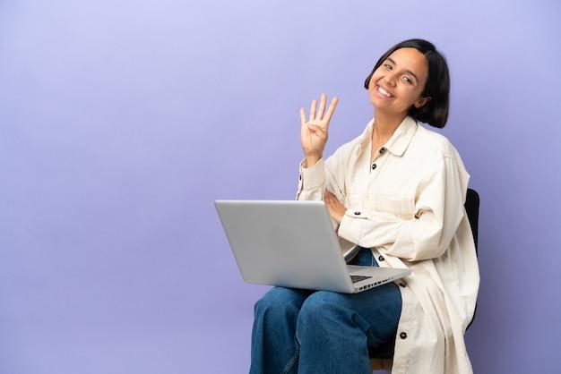 Молодая женщина смешанной расы сидит на стуле с ноутбуком, изолированным на фиолетовом фоне, счастлива и считает четыре пальцами