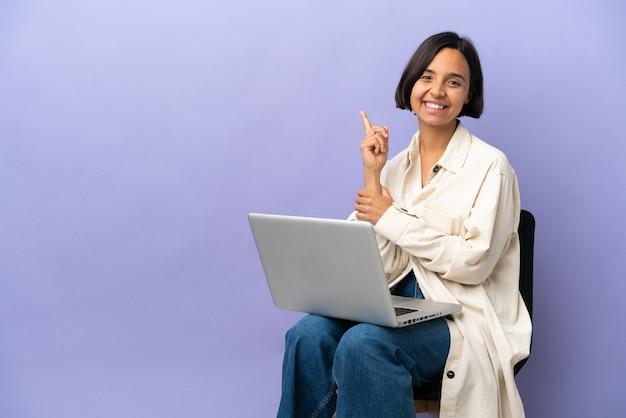 Молодая женщина смешанной расы, сидя на стуле с ноутбуком, изолированным на фиолетовом фоне, счастлива и указывая вверх