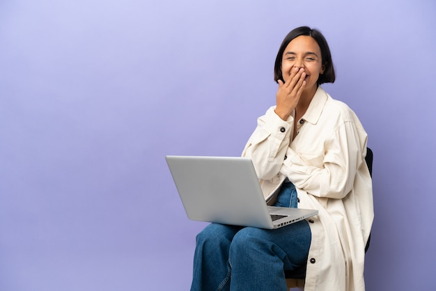 Молодая женщина смешанной расы, сидящая на стуле с ноутбуком, изолирована на фиолетовом фоне, счастливая и улыбающаяся, прикрывая рот рукой