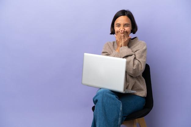 보라색 배경에 고립 된 노트북과 의자에 앉아 젊은 혼혈 여자가 행복하고 손으로 입을 덮고 웃고