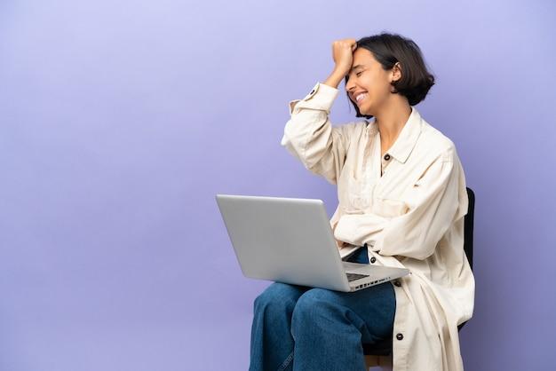 보라색 배경에 고립 된 노트북과 의자에 앉아 젊은 혼혈 여자는 뭔가를 실현하고 해결책을 계획하고 있습니다