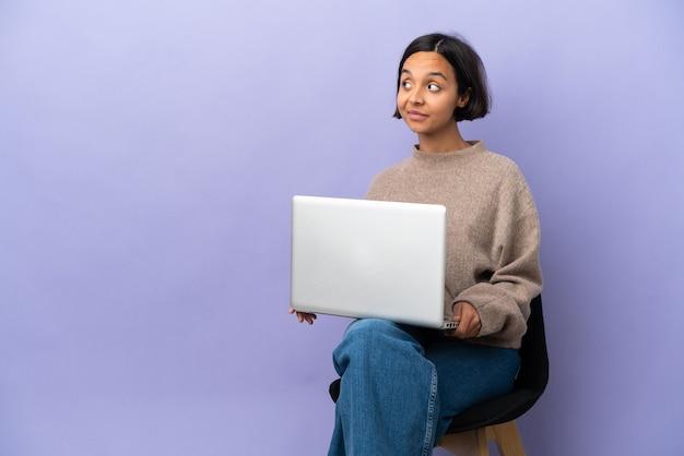 Молодая женщина смешанной расы сидит на стуле с ноутбуком, изолированным на фиолетовом фоне, сомневаясь, глядя в сторону