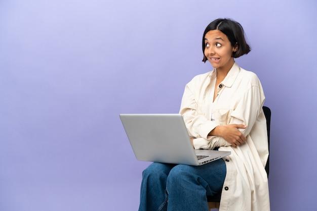 Молодая женщина смешанной расы сидит на стуле с ноутбуком, изолированным на фиолетовом фоне, сомневаясь, глядя вверх