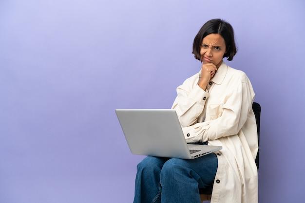 Молодая женщина смешанной расы сидит на стуле с ноутбуком, изолированным на фиолетовом фоне, сомневаясь