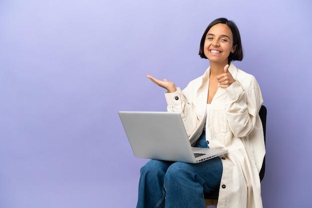 紫色の背景にノートパソコンを持って椅子に座った若い混血の女性が、手のひらに仮想のコピースペースを持ち、広告を挿入し、親指を立てた