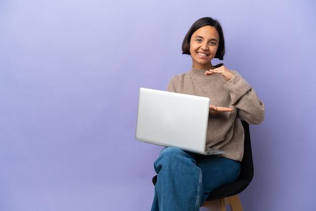 Молодая женщина смешанной расы сидит на стуле с ноутбуком, изолированным на фиолетовом фоне, держа на ладони воображаемое пространство, чтобы вставить объявление