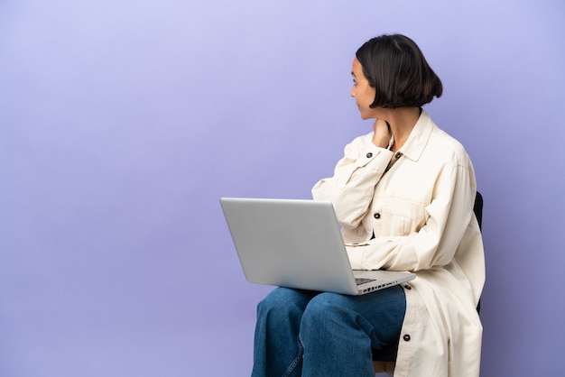Молодая женщина смешанной расы, сидящая на стуле с ноутбуком, изолирована на фиолетовом фоне в заднем положении и думает