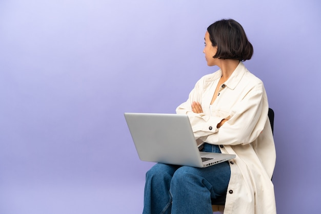 Молодая женщина смешанной расы, сидящая на стуле с ноутбуком, изолирована на фиолетовом фоне в заднем положении