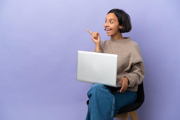 손가락을 들어 올리는 동안 솔루션을 실현하려는 보라색 배경에 고립 된 노트북과 의자에 앉아 젊은 혼혈 여자