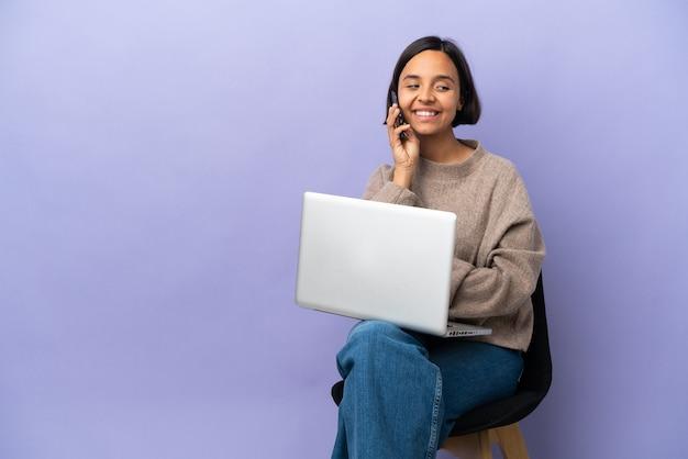 Молодая женщина смешанной расы сидит на стуле с ноутбуком, изолированным на фиолетовом фоне, разговаривает с кем-то по мобильному телефону