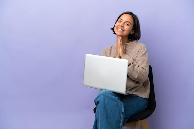 Молодая женщина смешанной расы, сидящая на стуле с ноутбуком, изолированным на фиолетовом фоне, держит ладонь вместе. человек о чем-то просит