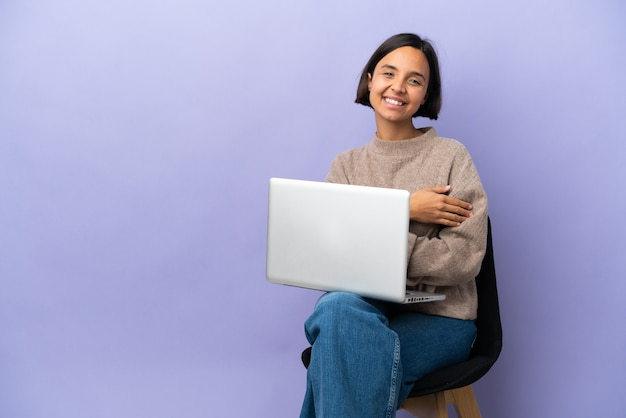 笑って紫色の背景に分離されたラップトップと椅子に座っている若い混血の女性
