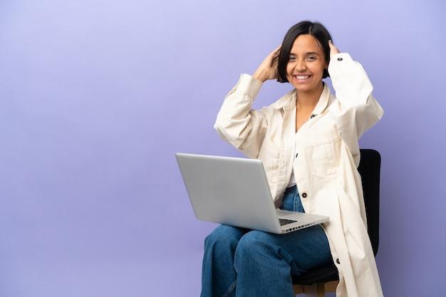 Молодая женщина смешанной расы сидит на стуле с ноутбуком, изолированным на фиолетовом фоне, смеясь