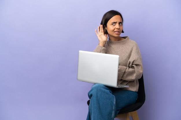 Молодая женщина смешанной расы сидит на стуле с ноутбуком, изолированным на фиолетовом фоне, слушая что-то, положив руку на ухо