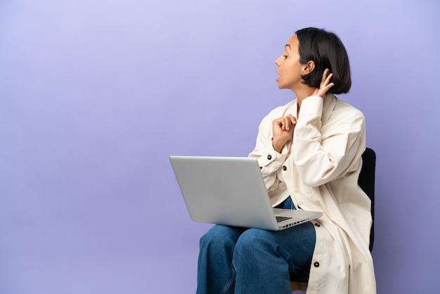젊은 혼혈 여자는 귀에 손을 넣어 뭔가를 듣고 보라색 배경에 고립 된 노트북과 의자에 앉아