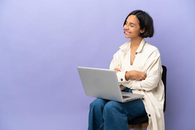 보라색 배경에 고립 된 노트북과 의자에 앉아 젊은 혼혈 여자가 측면을보고 웃