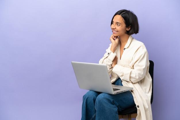 Молодая женщина смешанной расы сидит на стуле с ноутбуком, изолированным на фиолетовом фоне, глядя вверх, улыбаясь