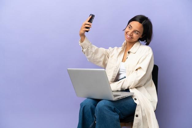 셀카를 만드는 보라색 배경에 고립 된 노트북과 의자에 앉아 젊은 혼혈 여자
