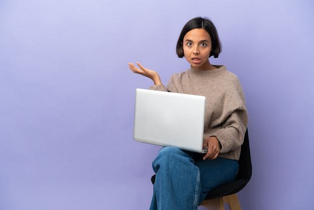 Молодая женщина смешанной расы сидит на стуле с ноутбуком, изолированным на фиолетовом фоне, делая жест сомнения
