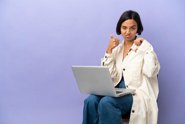 Молодая женщина смешанной расы, сидящая на стуле с ноутбуком, изолированным на фиолетовом фоне, делая знак