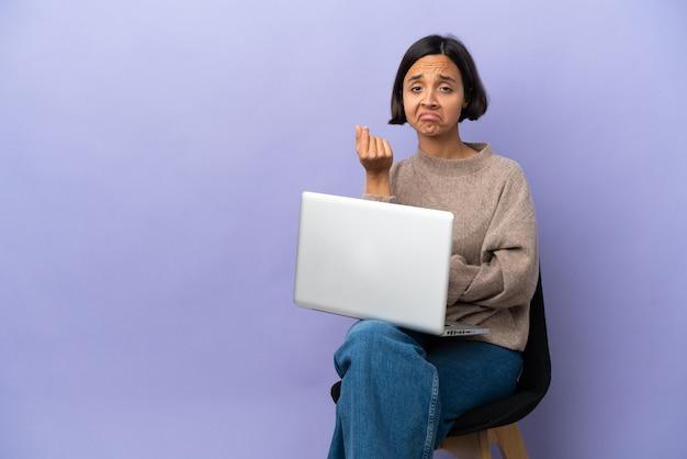 이탈리아 제스처를 만드는 보라색 배경에 고립 된 노트북과 의자에 앉아 젊은 혼혈 여자