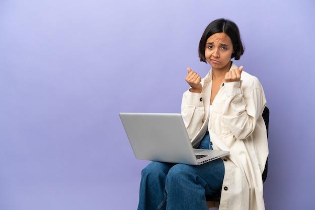 Молодая женщина смешанной расы сидит на стуле с ноутбуком, изолированным на фиолетовом фоне, делает денежный жест, но разрушена