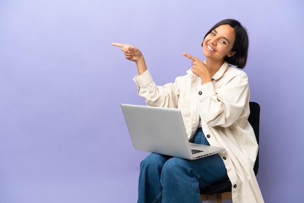 노트북과 의자에 앉아 젊은 혼합 된 경주 여자 측면에 손가락을 가리키는 보라색 배경에 고립 제품을 제시