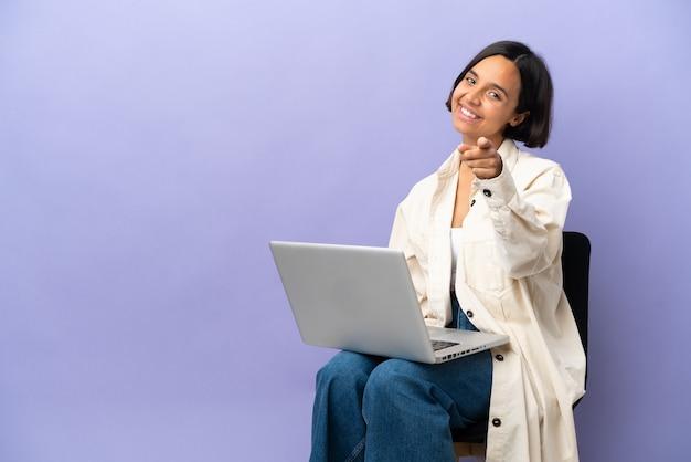Молодая женщина смешанной расы, сидящая на стуле с ноутбуком, изолирована на фиолетовом фоне, указывая вперед с счастливым выражением лица