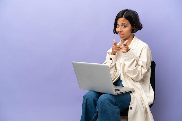 Молодая женщина смешанной расы сидит на стуле с ноутбуком, изолированным на фиолетовом фоне, указывая вперед и улыбается