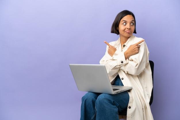 Молодая женщина смешанной расы сидит на стуле с ноутбуком, изолированным на фиолетовом фоне, указывая на боковые стороны, имеющие сомнения