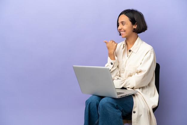 제품을 제시하기 위해 측면을 가리키는 보라색 배경에 고립 된 노트북과 의자에 앉아 젊은 혼혈 여자