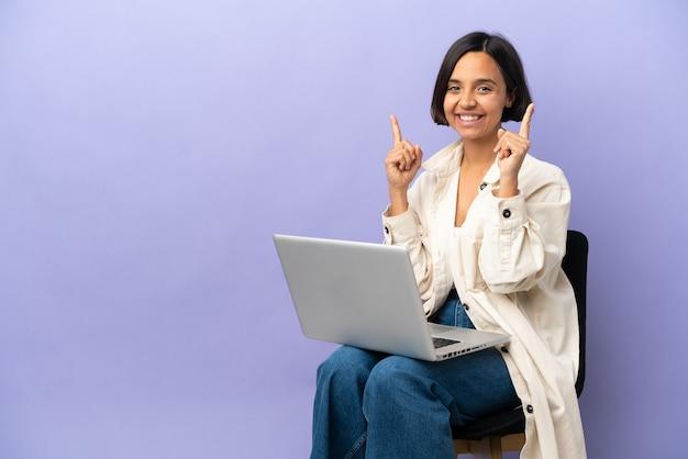 素晴らしいアイデアを指している紫色の背景に分離されたラップトップと椅子に座っている若い混血の女性