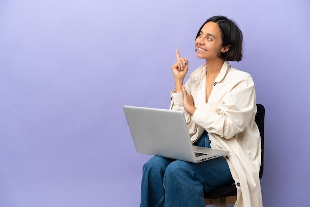 Молодая женщина смешанной расы, сидящая на стуле с ноутбуком, изолирована на фиолетовом фоне, указывая вверх отличную идею