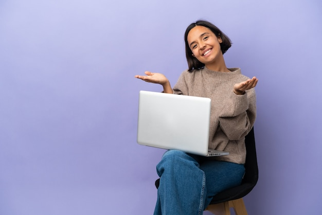 Молодая женщина смешанной расы сидит на стуле с ноутбуком, изолированным на фиолетовом фоне, представляет и приглашает прийти с рукой