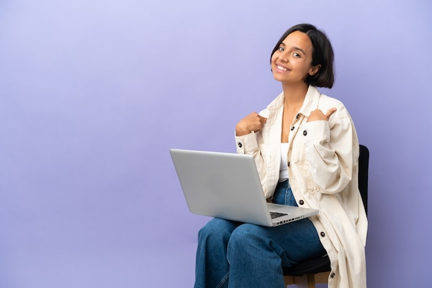 보라색 배경 자랑스럽고 자기 만족에 고립 된 노트북과 의자에 앉아 젊은 혼혈 여자