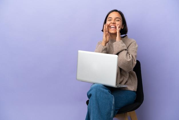 보라색 배경 소리와 뭔가 발표에 고립 된 노트북과 의자에 앉아 젊은 혼혈 여자