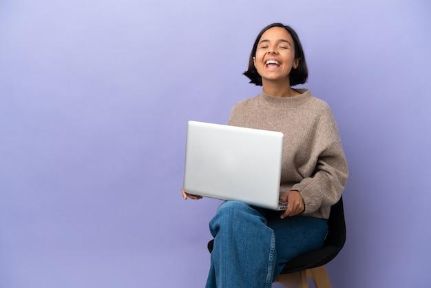 보라색 배경에 고립 된 노트북과 의자에 앉아 젊은 혼혈 여자 입 벌리고 전면에 외치는