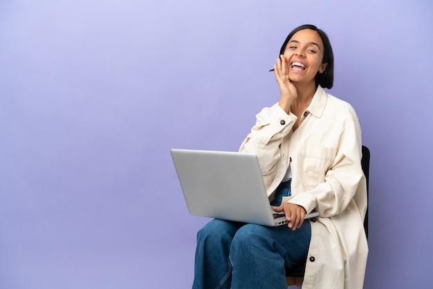 입 벌리고 외치는 보라색 배경에 고립 된 노트북과 의자에 앉아 젊은 혼혈 여자