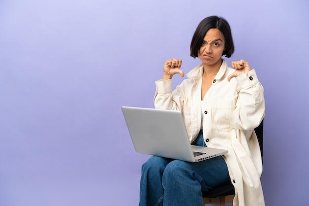 両手で親指を下に示す紫色の背景に分離されたラップトップと椅子に座っている若い混血の女性